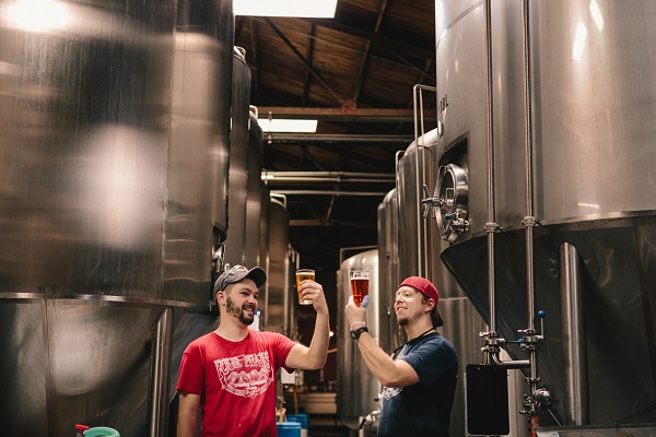 Two men making beer in a brewery