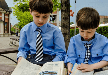 two school kids reading on a bench