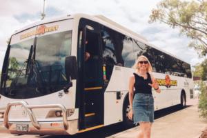 Lady disembarking a Horizons West bus waving